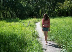 Girl walking on summer path